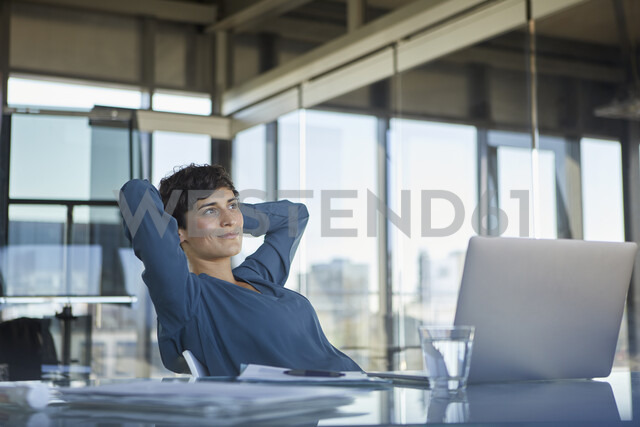 Smiling businesswoman sitting at desk in office with laptop having a break - RBF06910 - Rainer Berg/Westend61