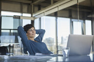 Smiling businesswoman sitting at desk in office with laptop having a break - RBF06910