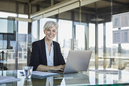 Portrait of confident businesswoman sitting at desk in office with laptop - RBF06916