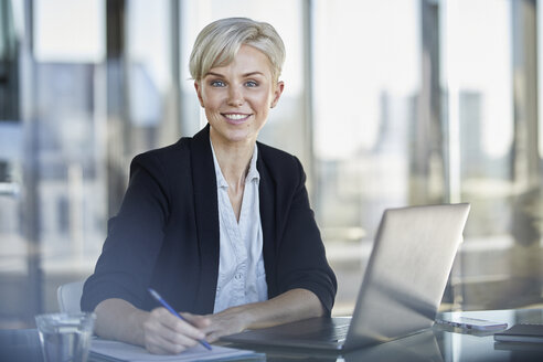 Portrait of confident businesswoman sitting at desk in office with laptop - RBF06919