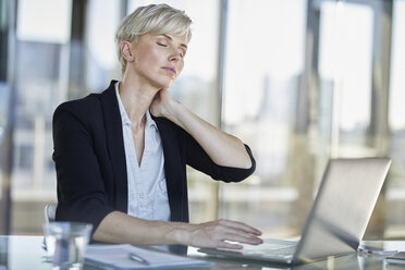 Exhausted businesswoman sitting at desk in office with closed eyes - RBF06922
