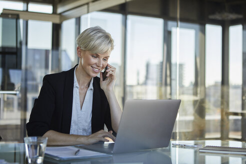 Smiling businesswoman working at desk in office - RBF06925