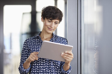 Smiling businesswoman using tablet at the window in office - RBF06931