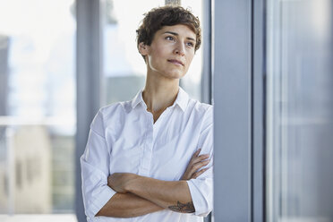 Businesswoman in office looking out of window - RBF06934