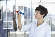 Businesswoman drawing chart on glass pane in office - RBF06940