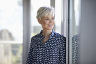 Smiling businesswoman in office looking out of window - RBF06946