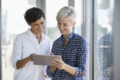 Two smiling businesswomen looking at tablet at the window in office - RBF06949