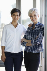 Portrait of two smiling businesswomen at the window in office - RBF06952