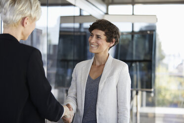 Two businesswomen shaking hands in office - RBF06958