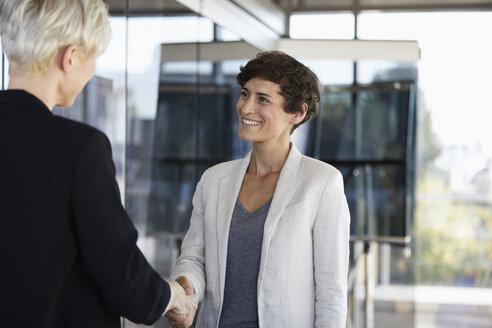 Two businesswomen shaking hands in office - RBF06958