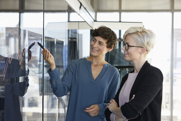 Two smiling businesswomen looking at chart on glass pane in office - RBF06961