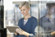 Businesswoman using tablet at the window - RBF06973