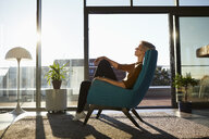 Woman sitting in armchair in sunlight with closed eyes - RBF06976
