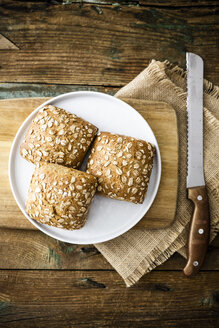 Three whole meal bread rolls with oat flakes on plate - GIOF05254