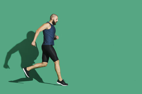 Bearded man jogging in front of green background - VGF00146