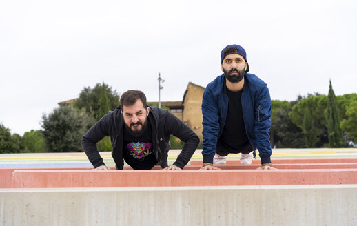 Portrait of two friends doing pushups side by side - AFVF02169