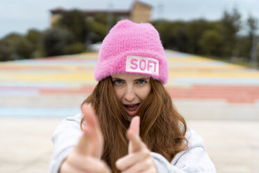 Portrait of redheaded woman wearing pink cap with the word 'soft' shooting at viewer - AFVF02178