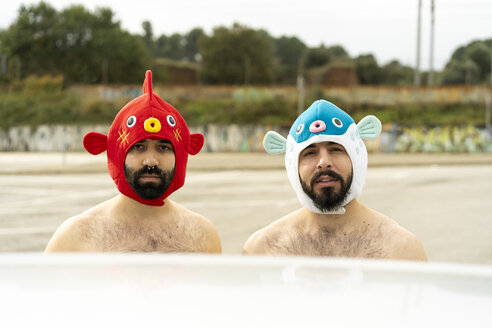 Portrait of shirtless gay couple wearing animal hats outdoors - AFVF02181
