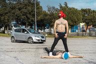 Gay couple wearing animal hats posing at car park - AFVF02184