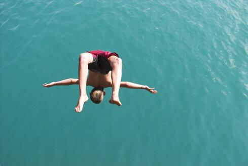 Boy having fun, jumping into Lake Wolfgangsee, Austria - WWF04587