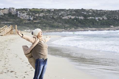 Spain, Menorca, happy senior man standing at seashore in winter - IGGF00698