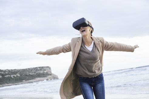 Spain, Menorca, senior woman using VR glasses on the beach in winter - IGGF00713