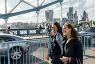 UK, London, two happy women walking on the Tower Bridge - MGOF03895