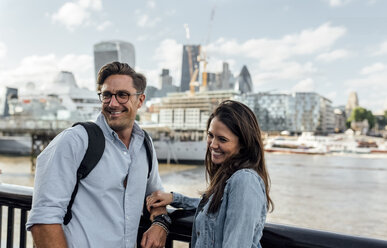 UK, London, smiling couple with skyline in the background - MGOF03898