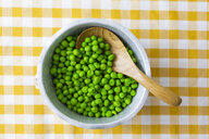 Peas in bowl, wooden spoon from above - GIOF05271