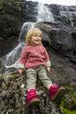 Denmark, Faroe islands, Estuyroy, Toddler in front of a waterfall - RUNF00545