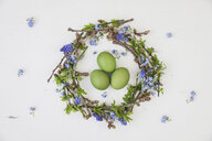 Self-made Easter wreath and green dyed eggs on white ground - GWF05747