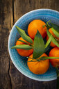 Clementines in bowl on wood, from above - LVF07615