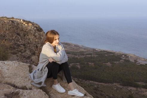 Spain, Alicante, Santa Pola, Cape Santa Pola, young woman sitting on rock at sunset - GRSF00037
