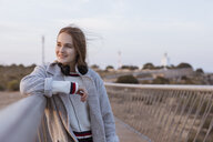Smiling young woman on a footbridge at sunset - GRSF00043