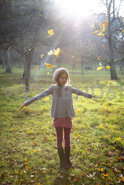 Young girl on meadow in autumn, autumn leaves - LVF07628 - Larissa Veronesi/Westend61