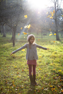 Young girl on meadow in autumn, autumn leaves - LVF07628