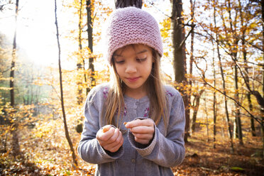 Young girl with beech nuts in autumn forest - LVF07631