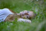 Portrait of happy teenage girl relaxing on a meadow in summer - LBF02314