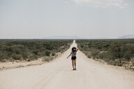 Namibia, woman walking on the road to Spitzkoppe - LHPF00339