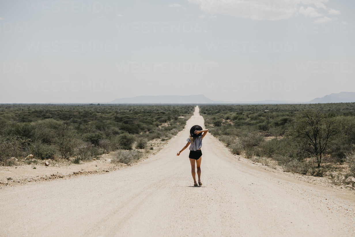 Namibia, woman walking on the road to Spitzkoppe - LHPF00339 - letizia haessig photography/Westend61