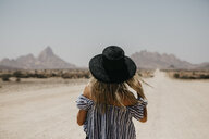 Namibia, woman wearing a hat on the road to Spitzkoppe - LHPF00342
