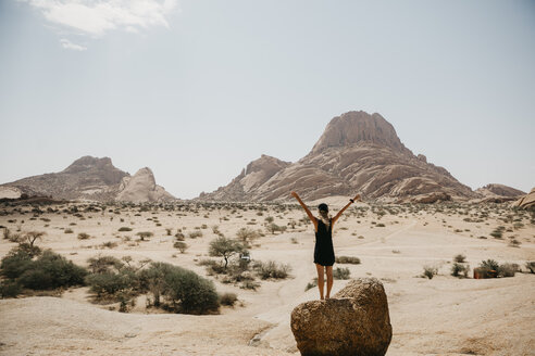 Namibia, Spitzkoppe, rear view of woman standing on rock with raised arms - LHPF00345