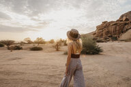 Namibia, Spitzkoppe, rear view of woman with hat at sunset - LHPF00360