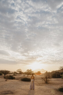 Namibia, Spitzkoppe, woman standing in desert landscape at sunset - LHPF00363