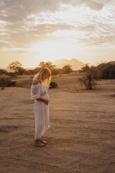 Namibia, Spitzkoppe, woman in white dress in desert landscape at sunset - LHPF00366