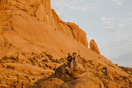 Namibia, Spitzkoppe, couple sitting on a rock at sunset - LHPF00369