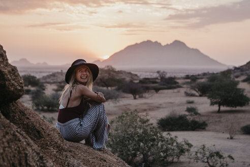 Namibia, Spitzkoppe, laughing woman sitting on a rock at sunset - LHPF00381