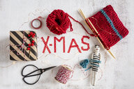 Wrapped Christmas present, knitting, scissors and small puppet on white wood - OJF00329