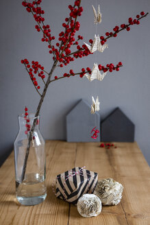 Wrapped present, paper decoration and twig of holly in vase - OJF00332
