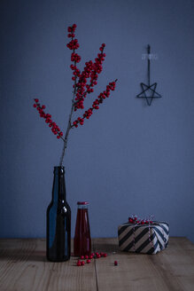 Twig of holly in glass bottle and wrapped present - OJF00335
